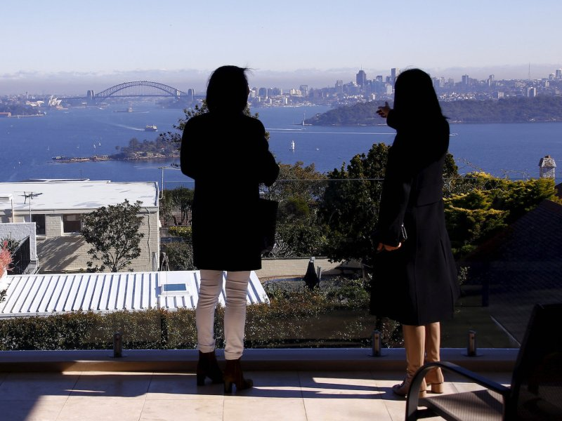 A real estate agent and potential Chinese home buyer from Shanghai look over the Sydney Opera House and Harbor Bridge in the Sydney suburb of Vaucluse, Australia, July 11, 2015. Photo: Reuters/David Gray