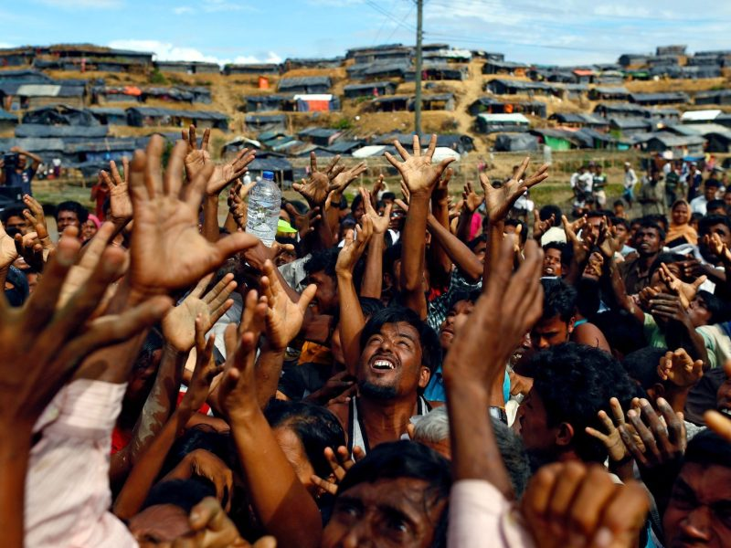 "Rohingya refugees stretch their hands to receive aid distributed by local organisations at Balukhali makeshift refugee camp in Cox's Bazar, Bangladesh, September 14, 2017. Reuters photographer Danish Siddiqui: ""I was going past one of the refugee camps when I stopped to photograph this aid distribution along a road. As the aid distribution got a bit chaotic, volunteers started throwing water bottles from the truck towards the refugees. I placed myself to get the newly made camp in the background as it showed how newly arrived Rohingyas living in these small makeshift shelters were in desperate need of aid."" REUTERS/Danish Siddiqui"