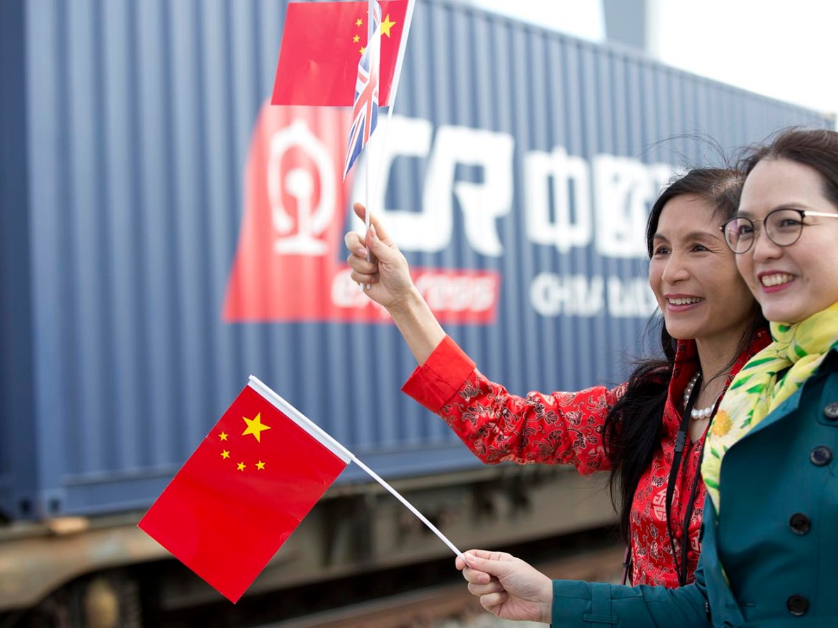 People wave Chinese and British flags at the departure of a freight train transporting containers from the UK on April 10, 2017, en route to Yiwu in China's Zhejiang province. Photo: AFP / Isabel Infantes