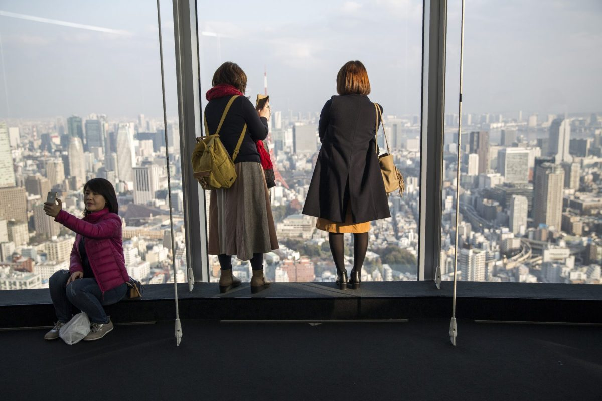 Visitors take selfies and pictures of the Tokyo skyline from the Roppongi Hills commercial complex on January 20, 2018. Photo: AFP / Behrouz MEHRI