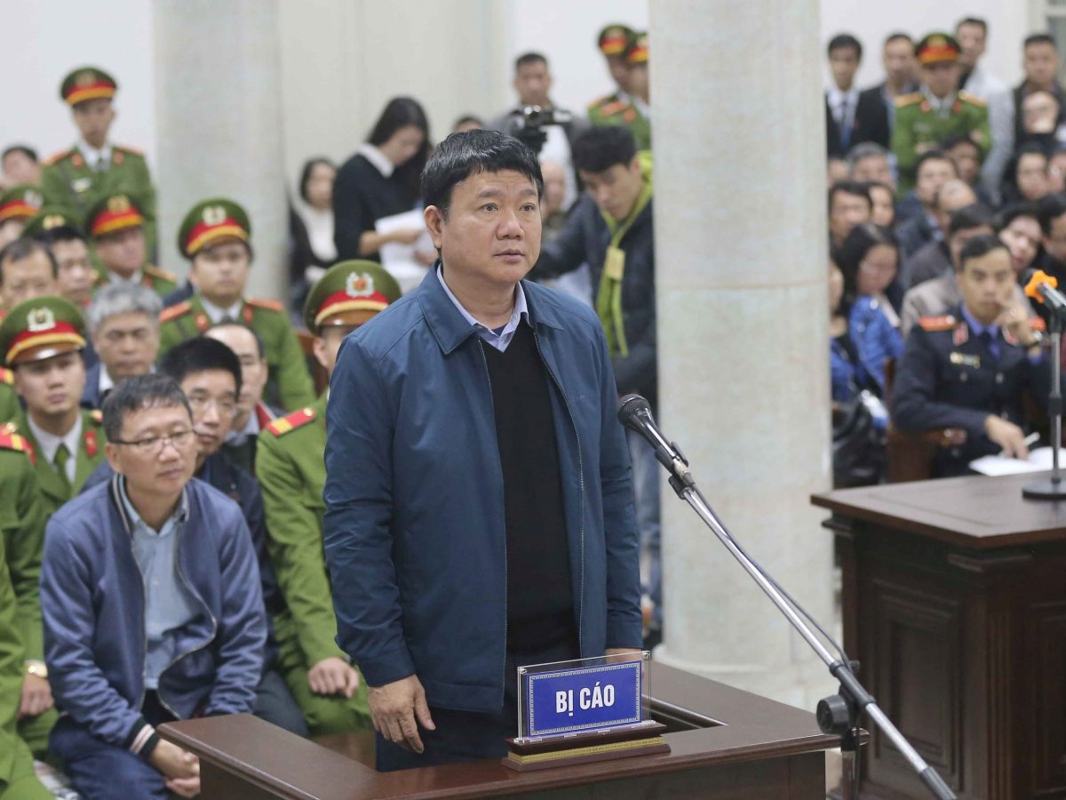 Dinh La Thang stands in court; behind him, PVC's former chairman, Trinh Xuan Thanh (left), sits. Photo: VNA/ Doan Tan via Reuters