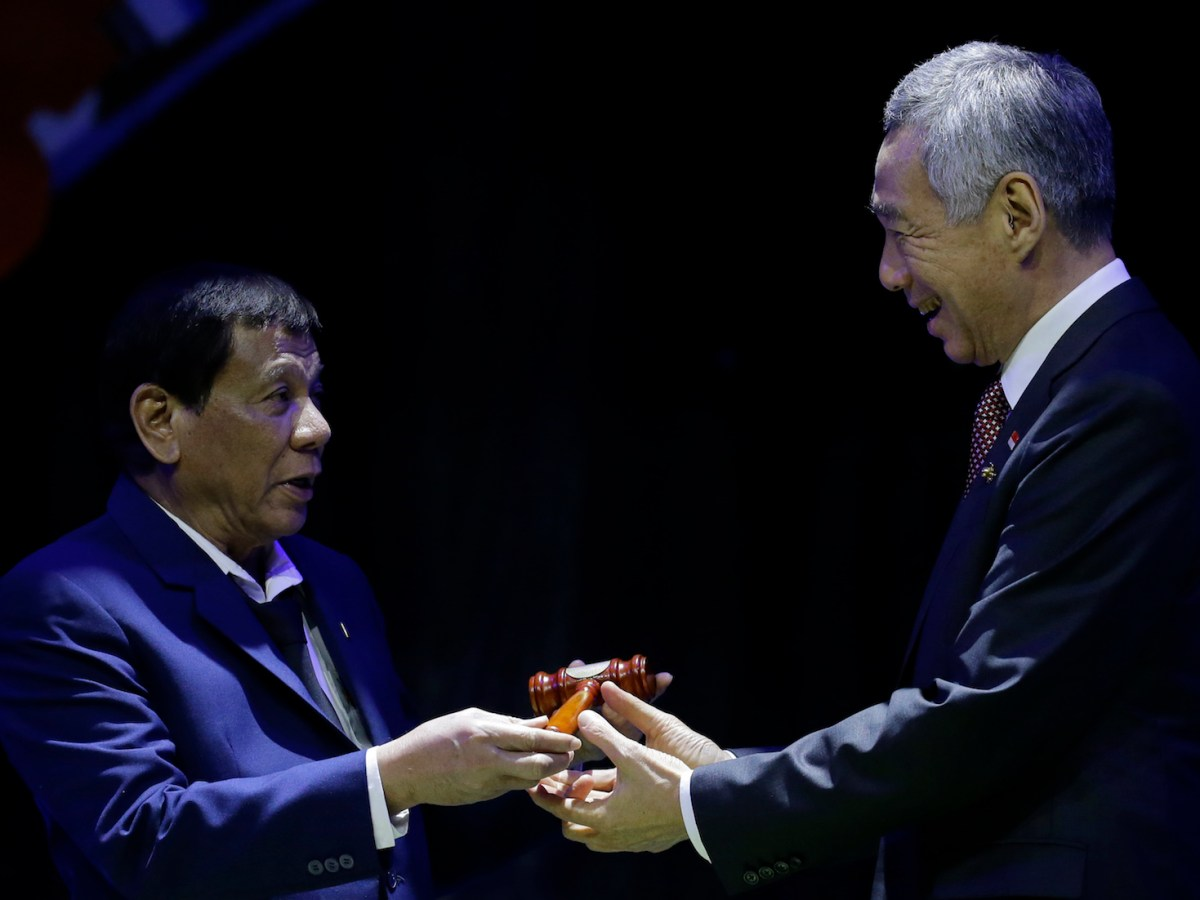 Philippine President Rodrigo Duterte (L) hands the gavel to Singapore Prime Minister Lee Hsien Loong during a transfer of Asean's chairmanship at the closing ceremonies of the grouping's 31st Summit in Manila on November 14, 2017. Photo: AFP/Aaron Favila/Pool