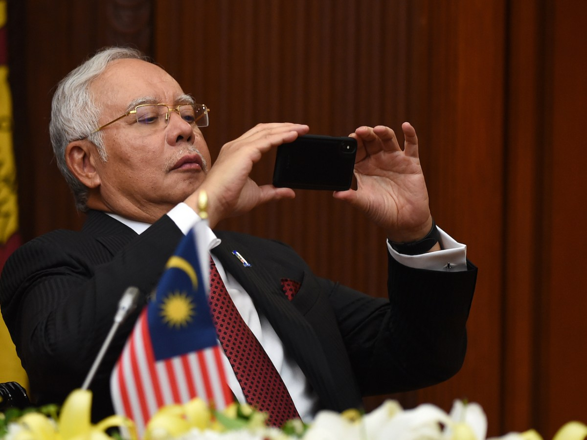 Malaysian Prime Minister Najib Razak takes a picture with his phone during a bilateral ceremony at the Presidential Secretariat in Colombo on December 18, 2017. Photo: AFP/Ishara S Kodikara