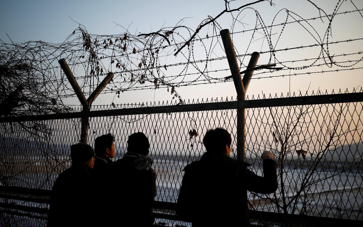 People look toward North Korea through a barbed-wire fence near the De-militarized Zone separating the two Koreas, in Paju, South Korea. Photo: Reuters / Kim Hong-Ji