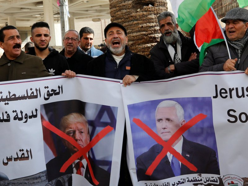 Palestinian demonstrators shout slogans as they hold crossed-out posters depicting US Vice-President Mike Pence and US President Donald Trump during a protest against Pence's visit to Israel, in the West Bank city of Nablus on January 22, 2018. Photo: Reuters / Abed Omar Qusini