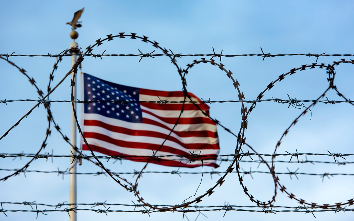 The US flag flies behind a foreground of razor wire. Photo: iStock