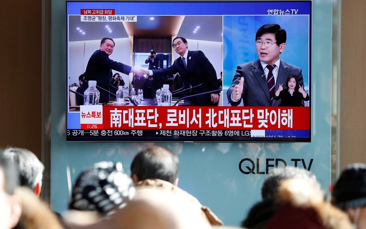 People watch a TV broadcasting a news report on a high-level talks between the two Koreas at the truce village of Panmunjom, in Seoul on January 9, 2018.   Photo: Reuters / Kim Hong-Ji