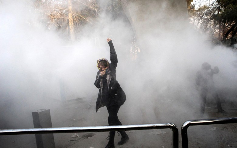 An Iranian woman raises her fist through the smoke of tear gas at the University of Tehran. Photo: AFP