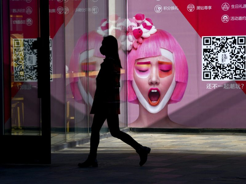 A woman walks past an advertisement at the entrance of a clothing store in Beijing on January 13, 2017. Photo: AFP / Wang Zhao