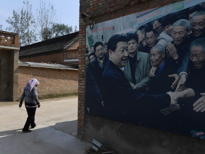 A man walks past a billboard featuring an image of China's President Xi Jinping visiting locals at a village in Lankao, in China's central Henan province. Photo: AFP