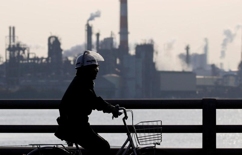 A worker cycles near a factory at the Keihin industrial zone in Kawasaki, Japan. Photo: Reuters/Toru Hanai
