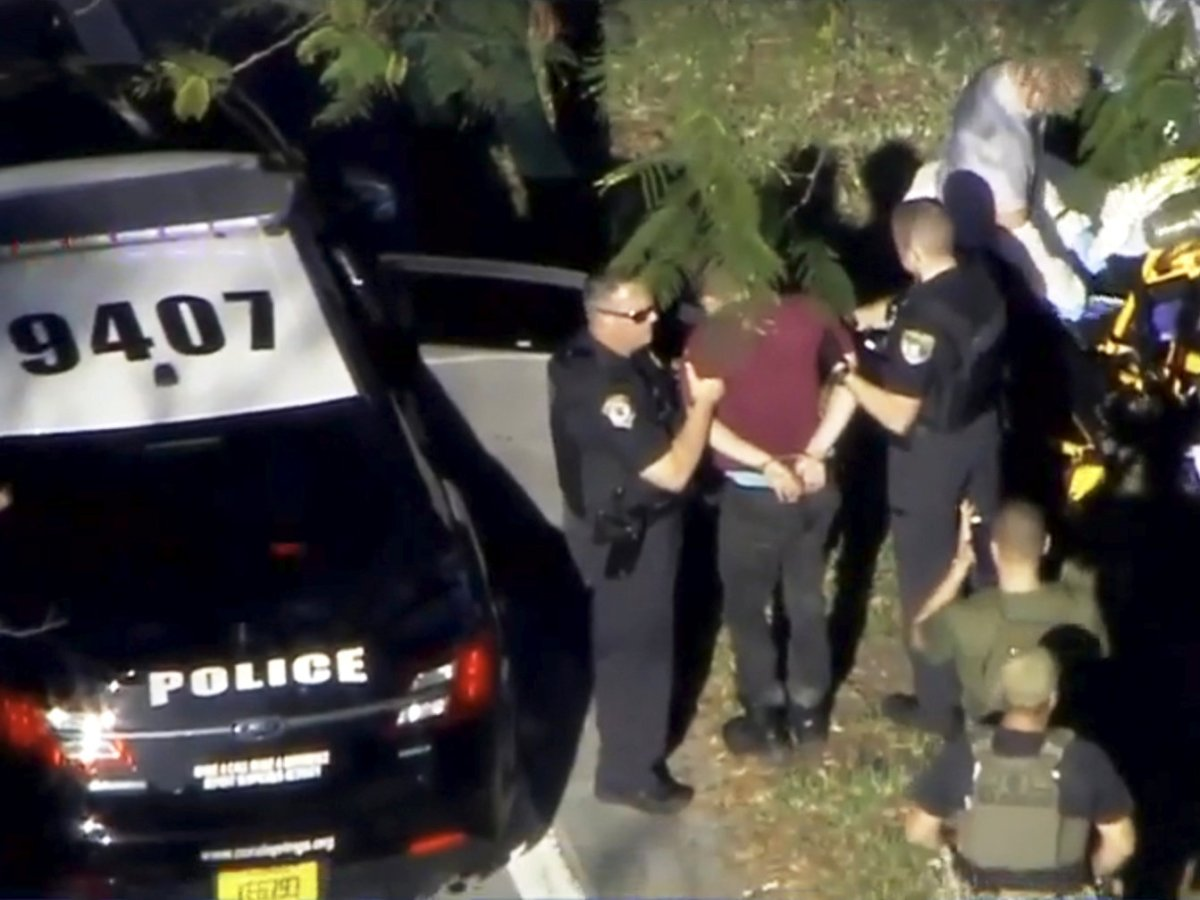 A man placed in handcuffs is led by police near Marjory Stoneman Douglas High School in Florida following a shooting incident. Photo: WSVN.com via Reuters