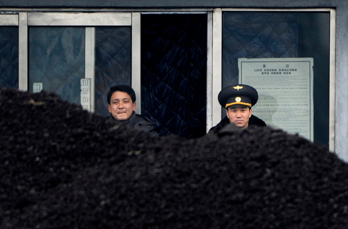 A North Korean military officer (R) and a North Korea man (L) stand behind a pile of coal along the banks of the Yalu River in the northeast of the North Korean border town of Siniuju in a 2012 file photo. Photo: AFP/Wang Zhao