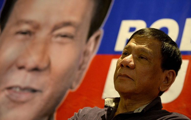 Then presidential aspirant Rodrigo Duterte stands in front of a campaign poster on November 30, 2015. Photo: AFP/Noel Celis