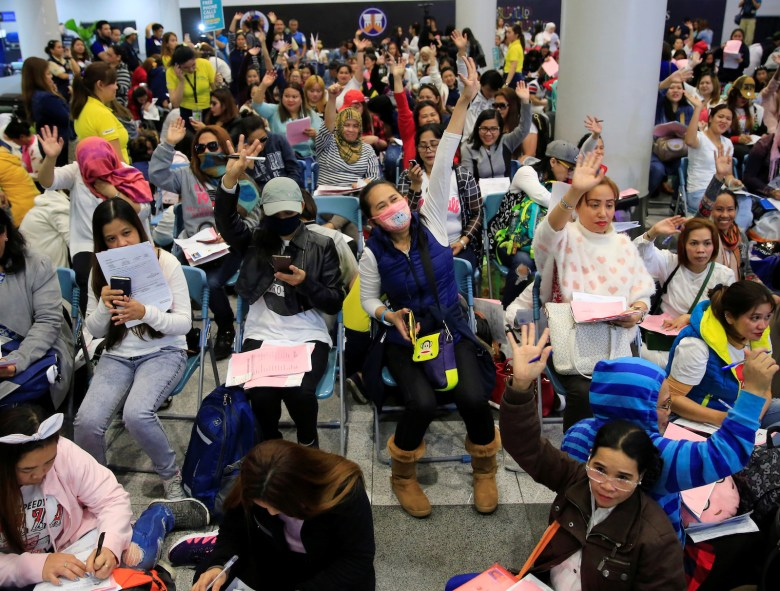 Overseas Filipino Workers (OFW) from Kuwait gather upon arrival at the Ninoy Aquino International Airport in Pasay city, Metro Manila, Philippines February 21, 2018. Following President Rodrigo Duterte's call to evacuate workers after a Filipina was found dead stuffed inside a freezer. REUTERS/Romeo Ranoco