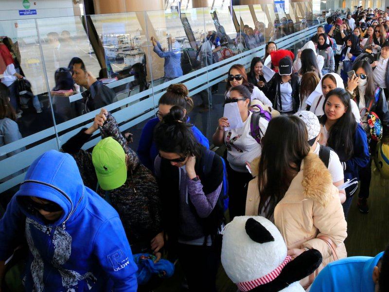 Around 190 Filipino workers from Kuwait arrive at the airport in Manila on Feb 23 following President Duterte's call for workers to be evacuated after a Filipina was found dead in a freezer. Photo: Reuters/ Romeo Ranoco