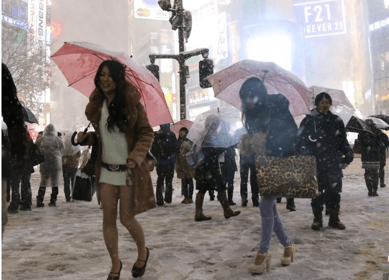 Young women wear short skirts during a snowy winter night in Tokyo. Photo: China News Service