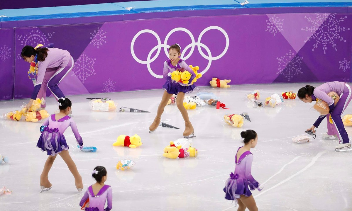 Korean girls pick up bears thrown onto the ice by fans of Yuzuru Hanyu of Japan after his Single Skating Short Program. Photo: Reuters / Damir Sagolj