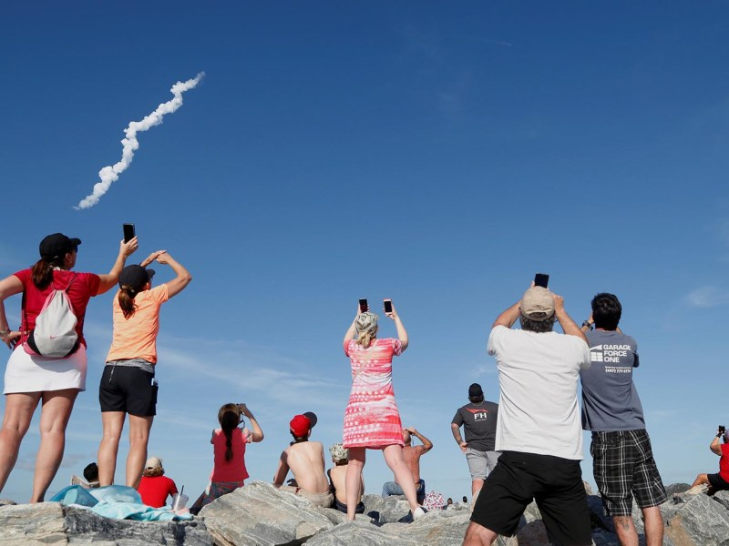 Spectators at Cocoa Beach watch SpaceX's first Falcon Heavy rocket launch from the Kennedy Space Center, Florida on February 6, 2018.  Photo: Reuters/Gregg Newton