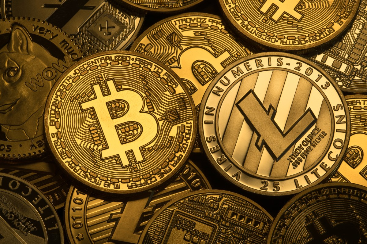 Cryptocyrrencies Bitcoin, Litecoin, Ethereum, dogecoin with trditional money. Photo: iStock