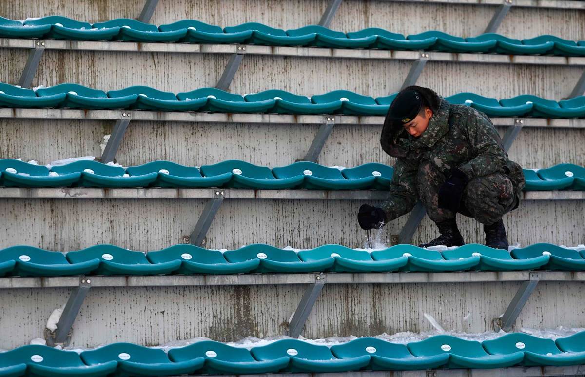 A South Korean soldier brushes snow off a seat in the spectator stands at the ski jump venue of the Pyeongchang Winter Olympics. Photo: Reuters/Kai Pfaffenbach