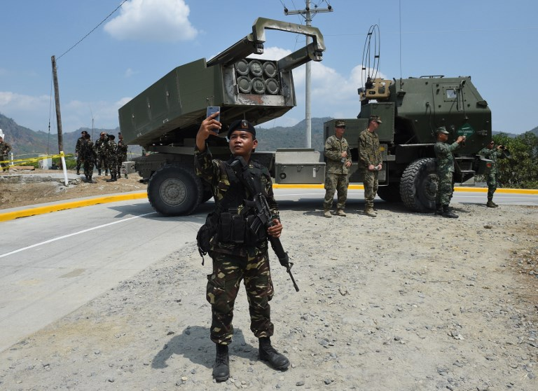 A Philippine soldier takes a selfie in front of an M142 High-Mobility Artillery Rocket System (HIMARS) after a live fire joint US-Philippine military exercise in 2016. Photo: AFP/Ted Aljibe