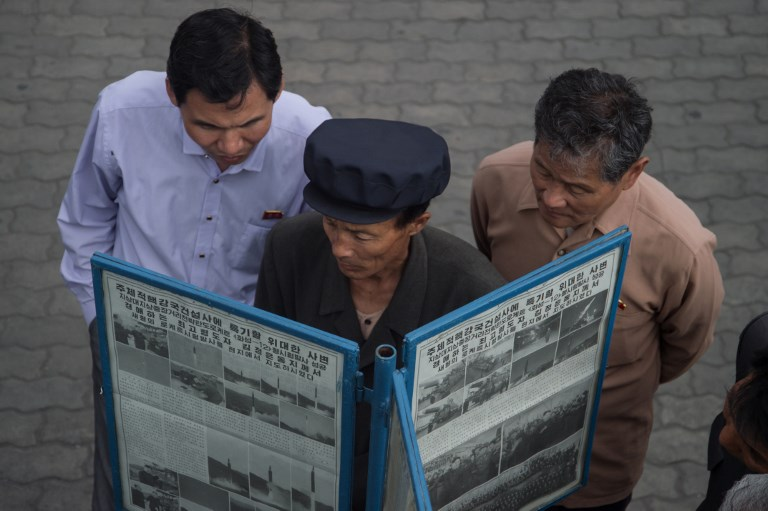 People gather at a street-side newsstand showing a copy of North Korea's Rodong Sinmun newspaper. Photo: AFP