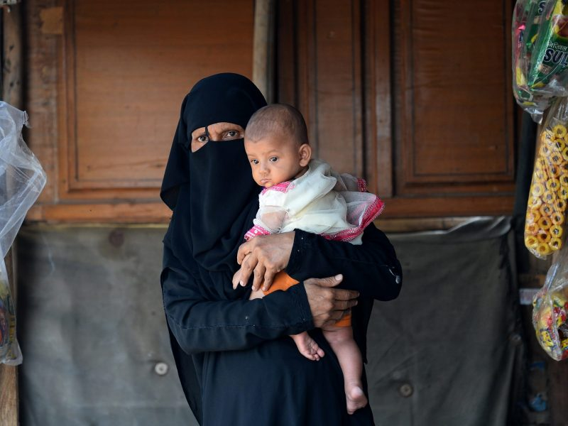A Rohingya refugee holds her child at a shop near their shelter in New Delhi. Photo: AFP/Sajjad Hussain