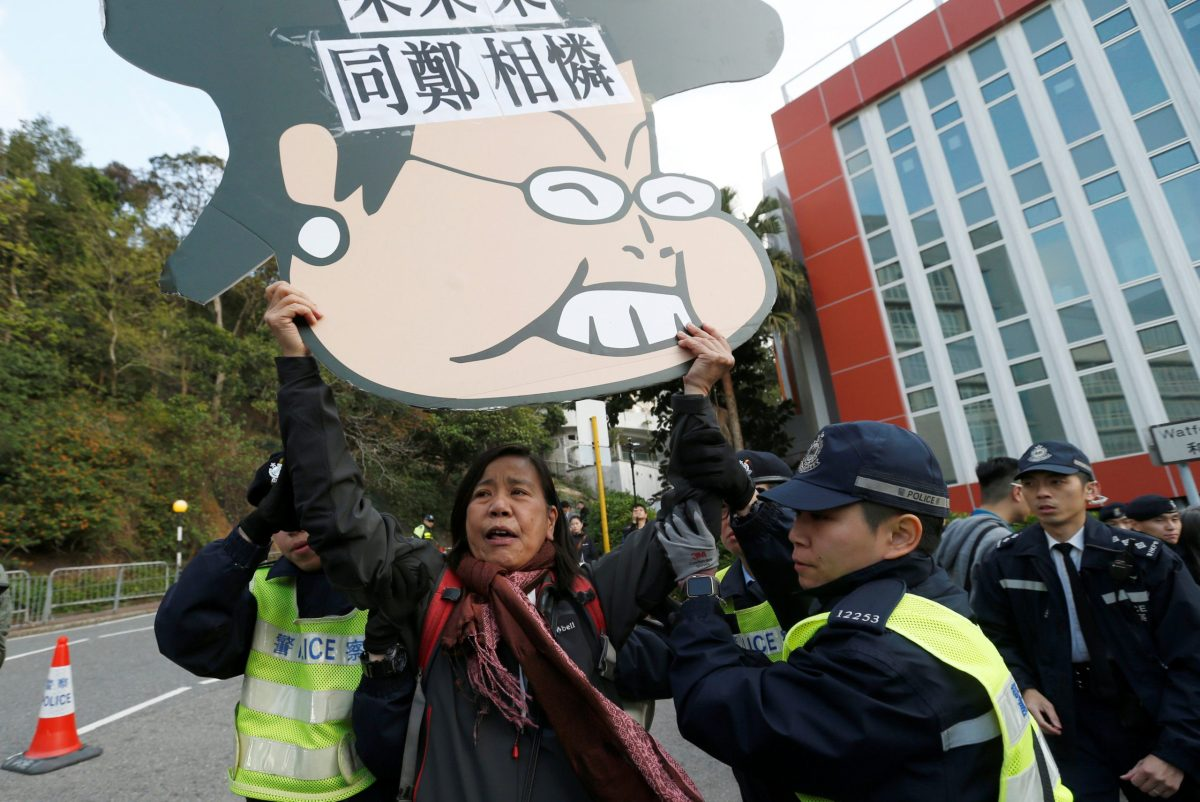 A pro-democracy protester carrying a cartoon of Hong Kong Chief Executive Carrie Lam is shepherded by police before Lam arrives to vote in a Legislative Council by-election on March 11, 2018.      Photo: Reuters / Bobby Yip