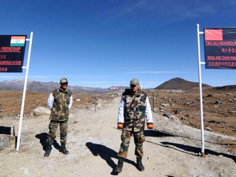 Soldiers stand guard at a border checkpoint on the Sino-Indian border. Signs bearing Chinese and Indian flags and bilingual slogans are in the background. Photo: AFP