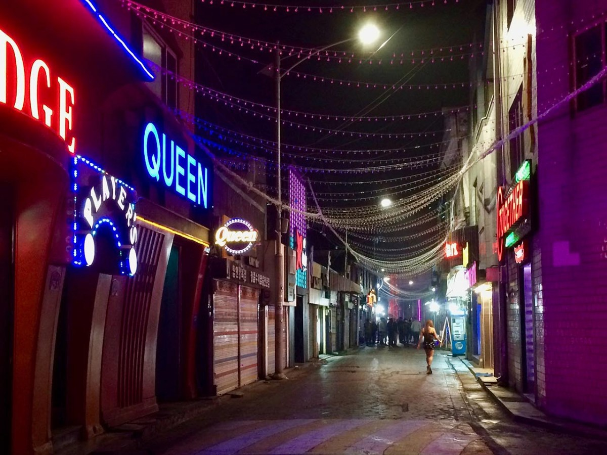 A lone bar girl stands in the once-raucous streets of Dongducheon's camp town. Troop relocations and a US Army crackdown on the sex trade has gutted the area's 'juicy bars.' Photo: Anouk Eigenraam / Asia Times