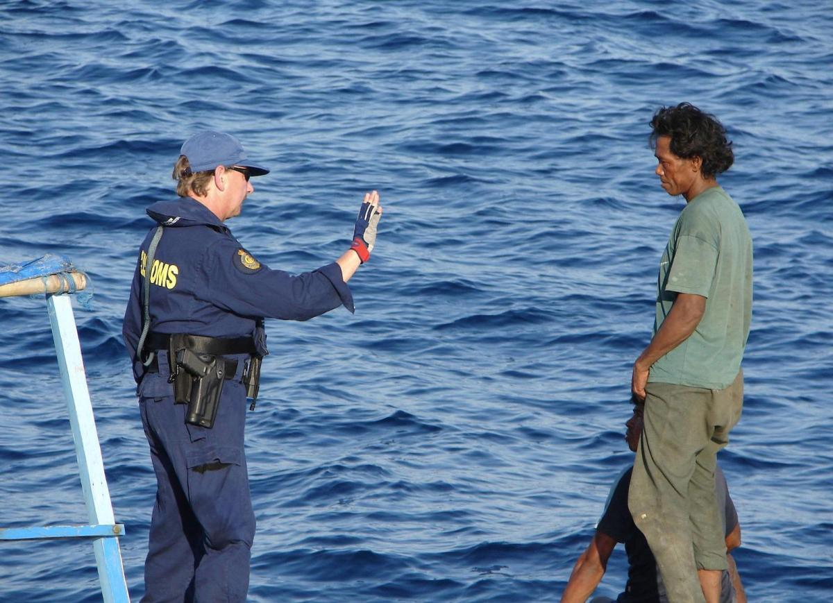 An Australian Customs officer with an Indonesian fisherman in waters near the two countries' maritime border in a file photo. Photo: AFP