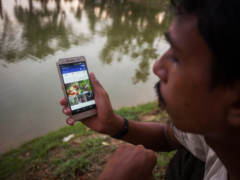 A Rohingya man looks at Facebook on his cell phone at a temporary makeshift camp after crossing over from Myanmar into the Bangladesh side of the border, near Cox's Bazar's Palangkhali, September 8, 2017. Photo: Nurphoto via AFP/ Ahmed Salahuddin