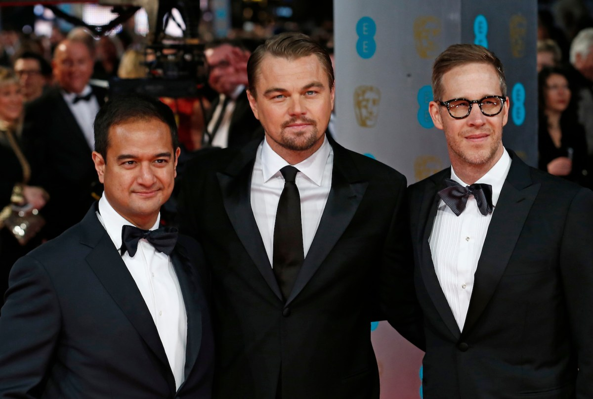 US producers Riza Aziz (L) and Joey McFarland (R) with US actor Leonardo DiCaprio (C) arriving on the red carpet for the BAFTA British Academy Film Awards at the Royal Opera House in London on February 16, 2014. AFP PHOTO / ANDREW COWIE / AFP PHOTO / ANDREW COWIE