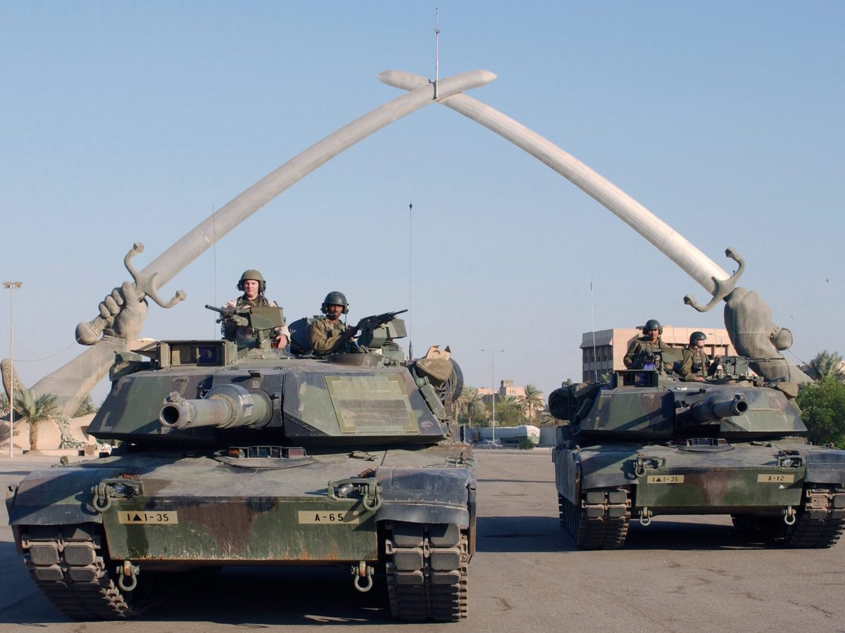 """US tanks pose for a photo under the """"Hands of Victory"""" in Ceremony Square, Baghdad, Iraq. Photo: US Air Force/John L Houghton"""