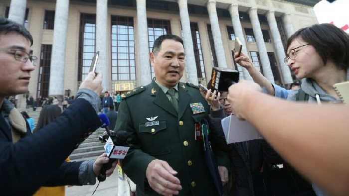 Former PLA Lieutenant-General Wang Hongguang is surrounded by reporters in front of the Great Hall of the People in Beijing. Photo: China Central Television screen grab