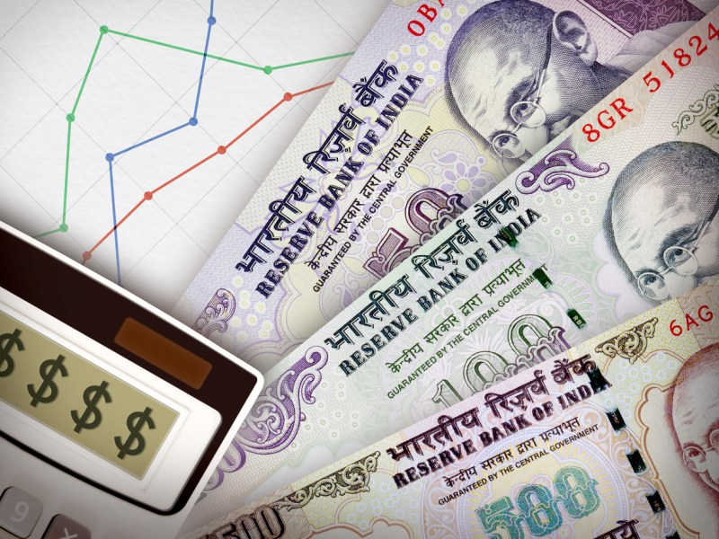 Three banknotes in front of sheet of paper with a graph on it symbolizing economic relationships. Photo: iStock