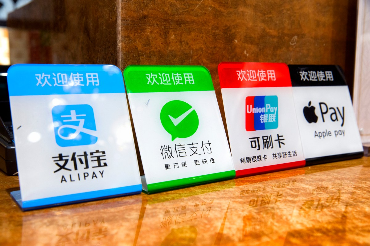 Signs indicating the available electronic payment methods in a store in China : Alipay, WeChat pay, Western Union card, and Apple pay. Photo: iStock