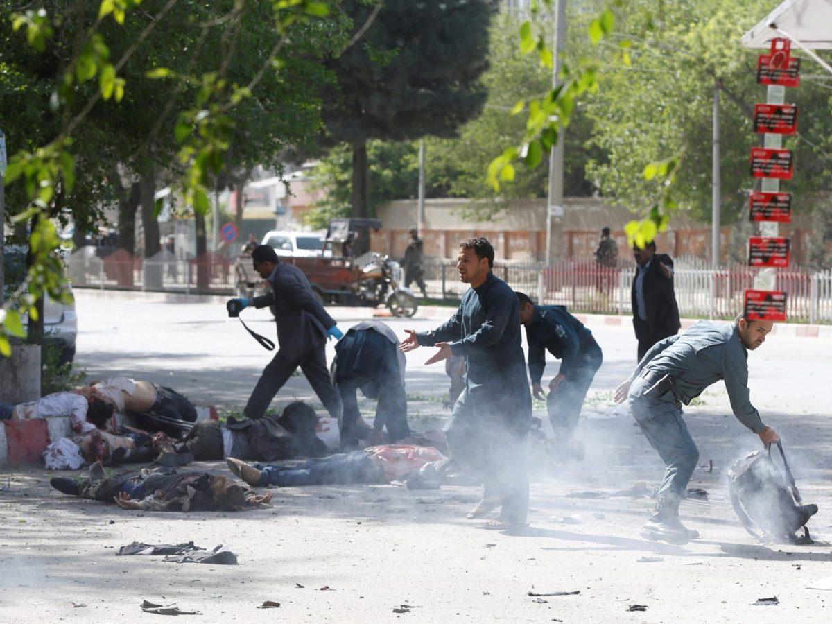 Police try to help wounded Afghan journalists, victims of a second blast, in Kabul on Monday. Photo: Reuters/Omar Sobhani