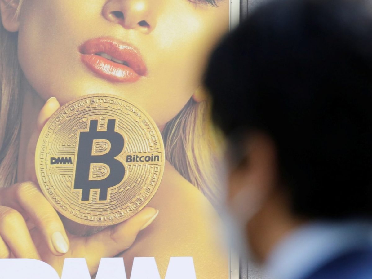 A man stands near an ad for a crypto-currency exchange in Tokyo on March 30. Photo: Reuters / Toru Hanai