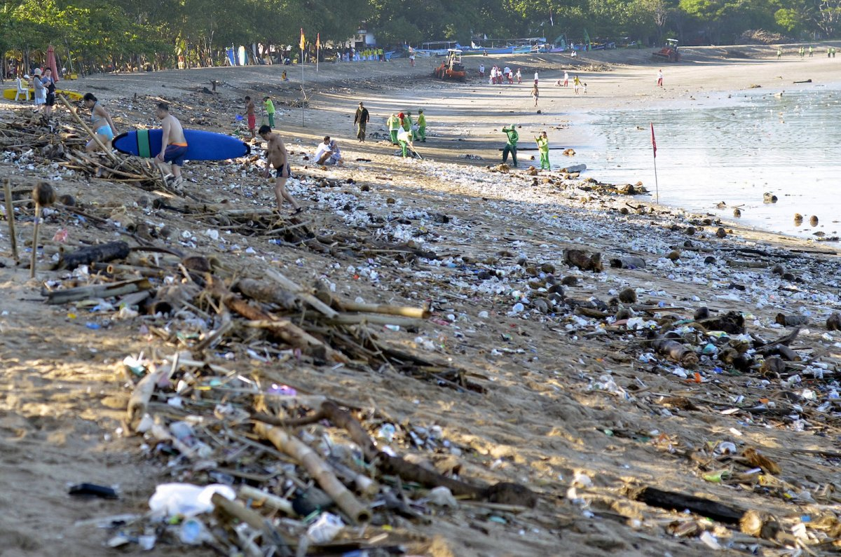 Tourists walk amongst trash washed up on Bali's Kuta beach pushed to shore by seasonal winds. Photo: Reuters/Wira Suryantala/Antara Foto
