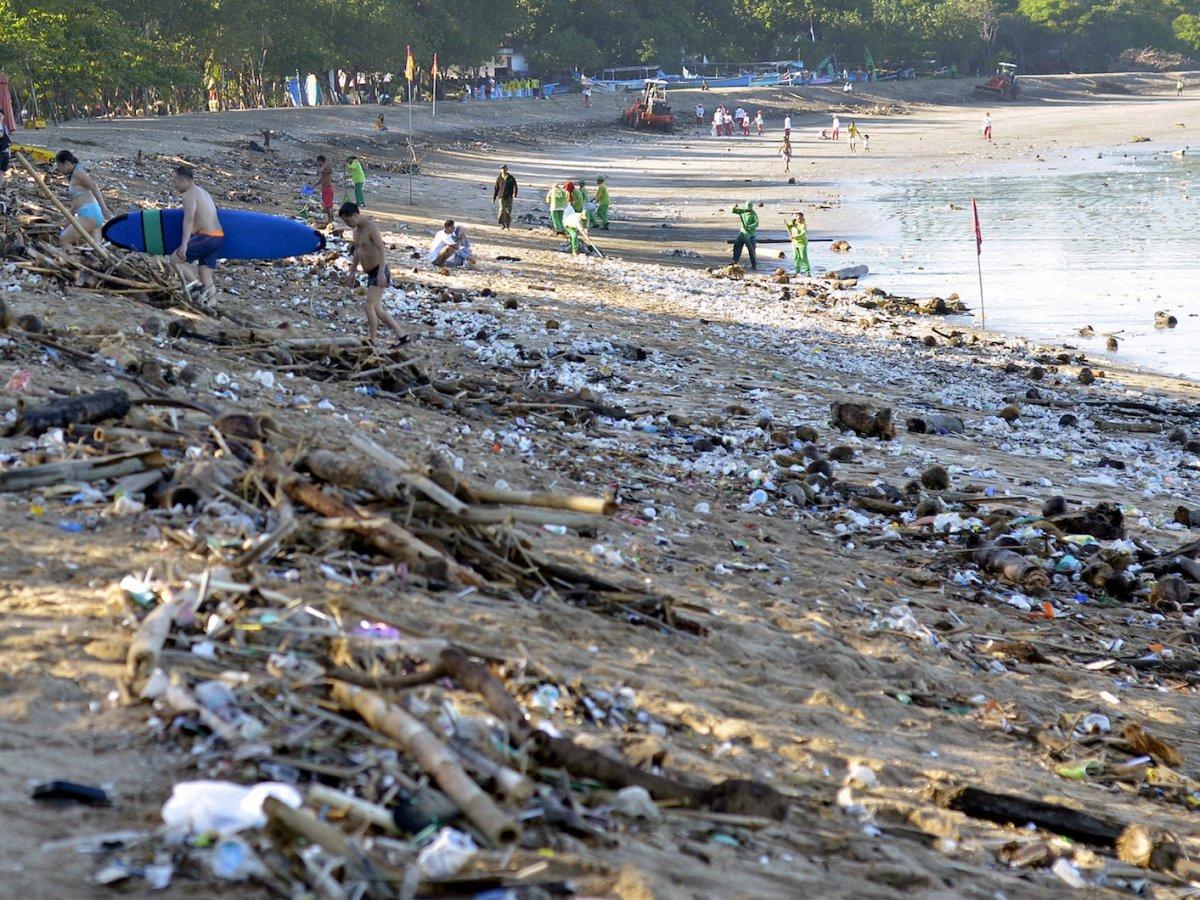 Tourists walk amongst trash washed up on Bali's Kuta beach pushed to shore by seasonal winds. Photo: Reuters/Wira Suryantala/Antara Foto