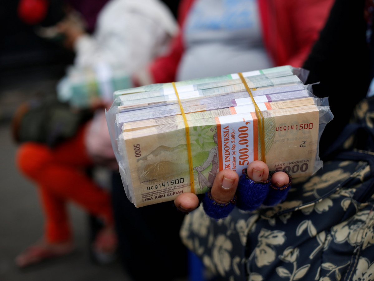 A woman holds a large stack of Indonesian rupiah bank notes in a street in Jakarta, Indonesia, April 27, 2018. Reuters/Willy Kurniawan