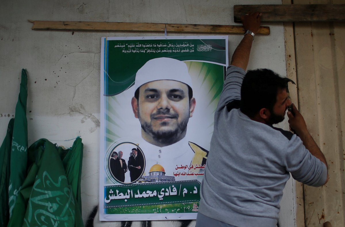 A man hangs a poster depicting Palestinian electrical engineer Fadi al-Batash, who was shot to death in Malaysia, on his family house in the northern Gaza Strip April 21, 2018. Photo: Reuters/Mohammed Salem