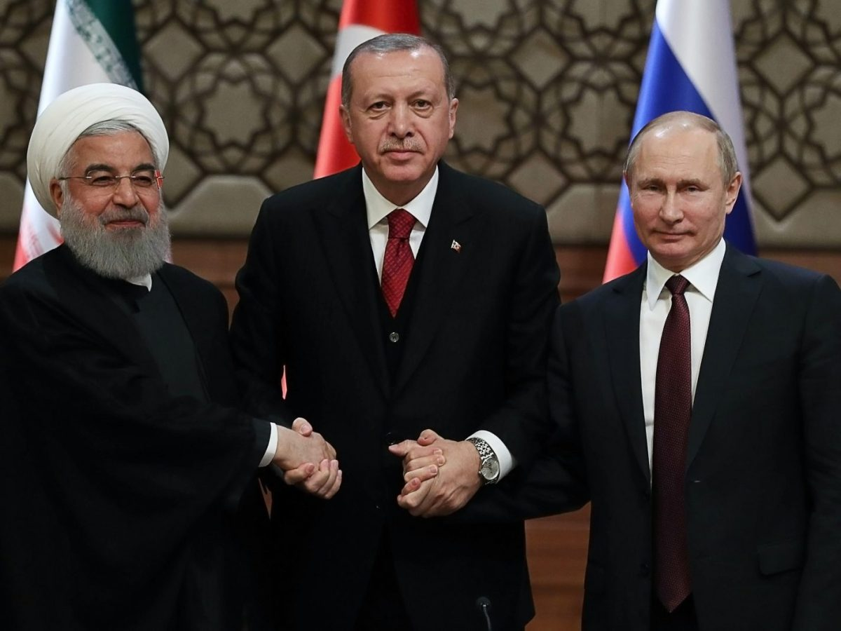 Turkish President Recep Tayyip Erdogan holds hands with Iran's President Hassan Rouhani, left, and Russian President Vladimir Putin after a summit on Syria on April 4. Photo: AFP / Adem Altan