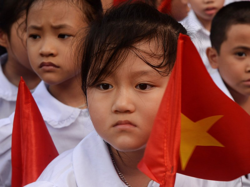 Pupils wave national flags during a ceremony at a local elementary school in Hanoi, Vietnam, on September 5, 2014. Photo: AFP/Hoang Dinh Nam