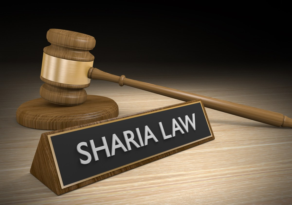 Religious Islamic law concept of a wooden court gavel lying beside a sign that reads Sharia law. Photo: iStock