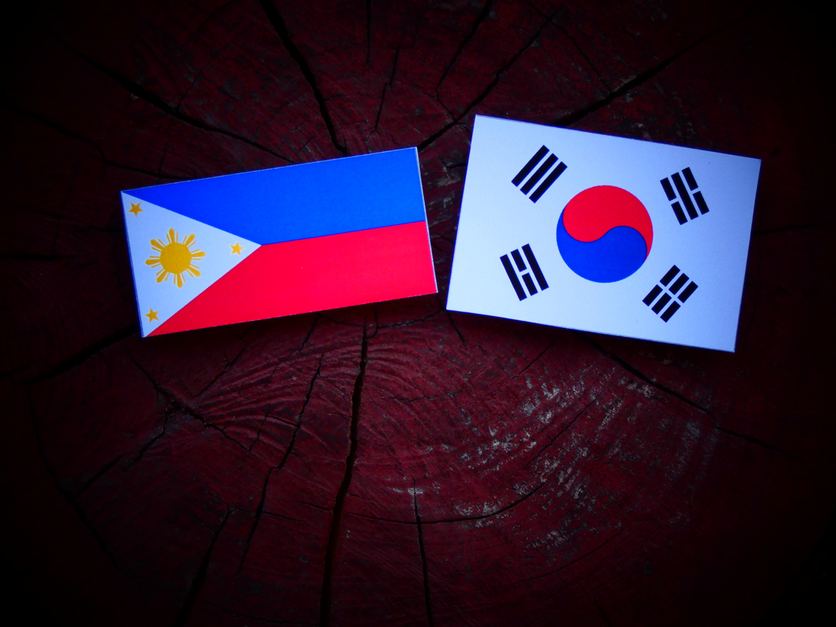 Philippines flag with South Korean flag on a tree stump isolated. Photo: iStock