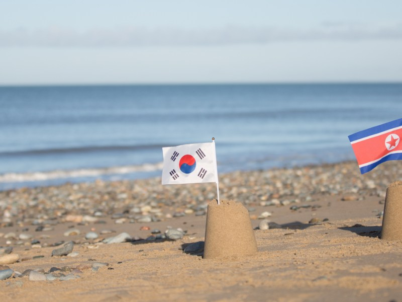 North and South Korean flags on beautiful beach. Photo: iStock