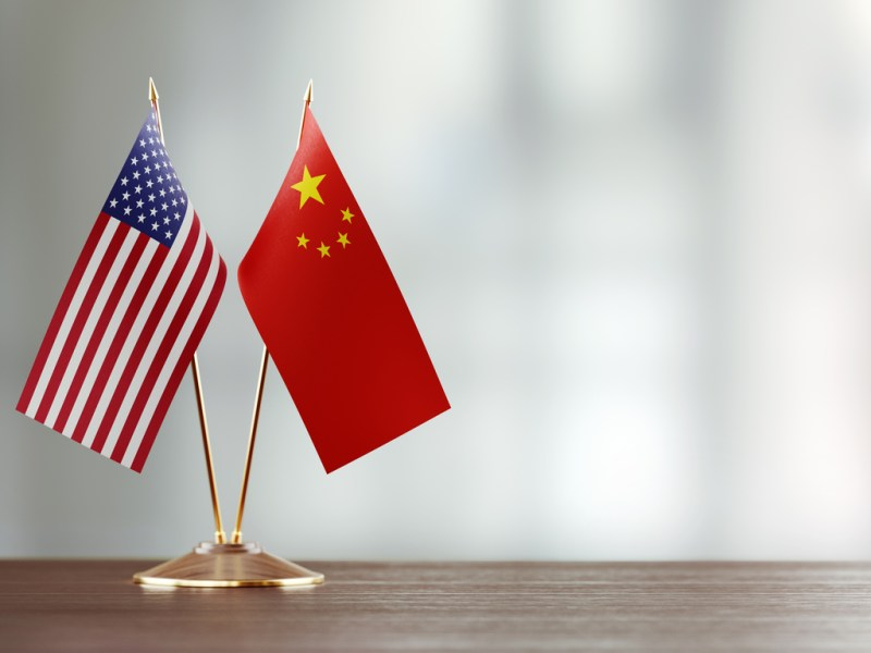 American and Chinese flag pair on desk over defocused background. Horizontal composition with copy space and selective focus.Photo: iStock